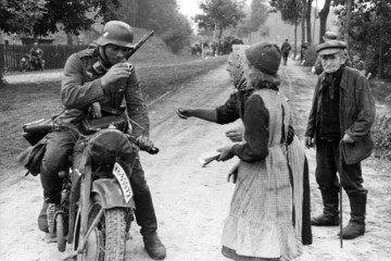 A German soldier with civilians in September 1939 during the German invasion of Poland