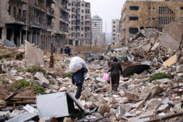 people walking down destroyed street in Aleppo
