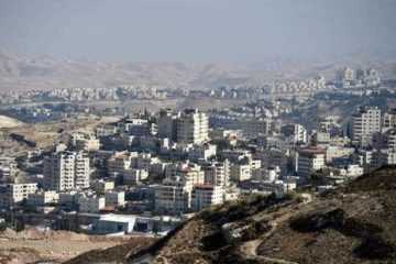 view of arab village with Israeli settlements on hilltops behind