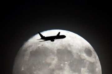 Plane silhouetted against the moon