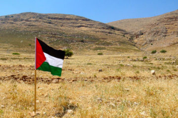 Palestinian flag with hills in the background