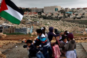 Palestinian kids playing in front of a Palestinian flag with an Israeli settlement in the background