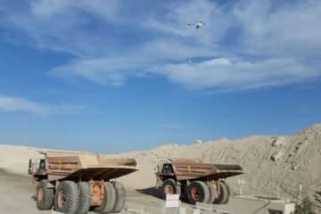 drone over large mining trucks