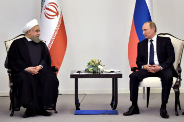 Iranian President Hassan Rouhani talks to Russian President Vladimir Putin during a meeting in Baku, Azerbaijan on August 8 2016.