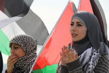 Palestinian women in front of their flag