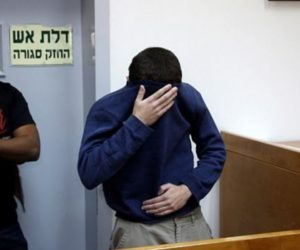 Kadar covering his face appearing in court