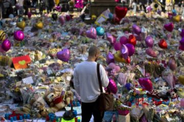 man standing in front of masses of floral tributes at Manchester