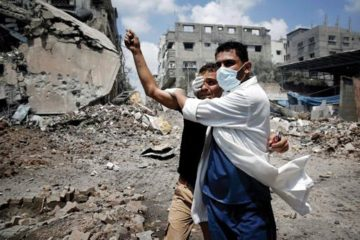 A doctor covering a man's eye in front of rubble