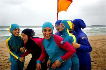 muslim girls in modest beachwear playing at beach