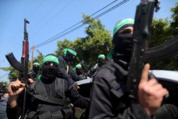 masked hamas members with guns close up at a rally