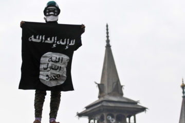 lone person standing holding a terror sign with their face covered