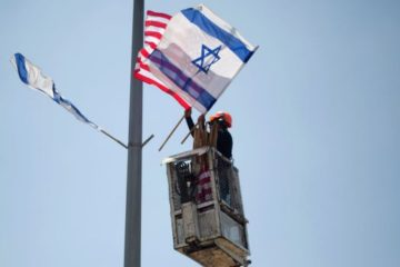 worker hanging american and israeli flags