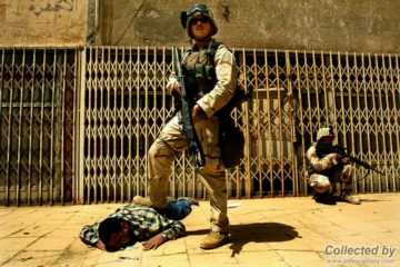 US marine standing with his foot on an Iraqi lying on the ground