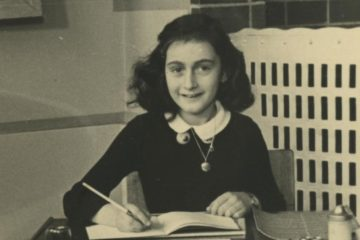Anne smiling into the camera with open book and pencil in hand
