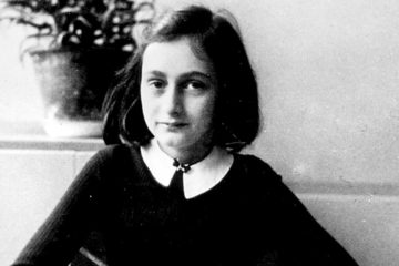 Anne Frank, pen in hand looking at the camera