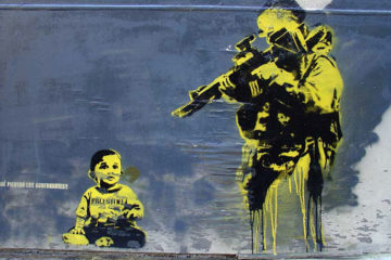 graffiti of a soldier pointing a gun at a baby