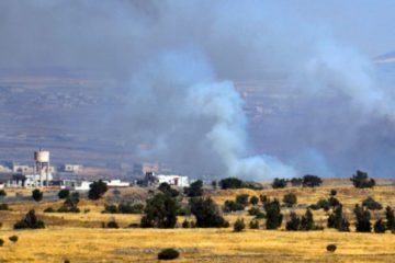 smoke billowing in distant Syria