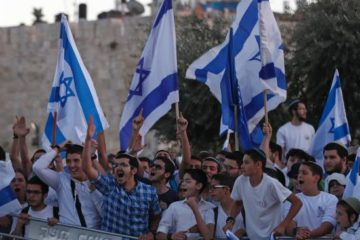 Israelis with flags protesting in front of old city walls