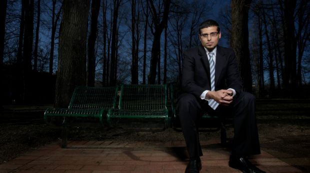 Manny Waks sitting on a park bench in the dark
