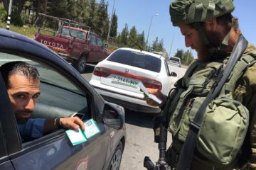 israeli soldier checking palestinian ID papers through window of car