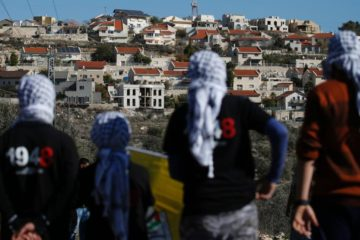 palestinian protesters in foreground facing an israeli settlement in the distance