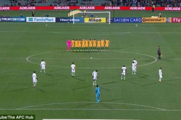 aussie soccer team standing for minute silence and saudi players scattered across the field