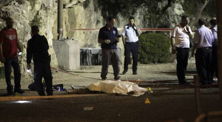 police stand around covered body outside old city walls