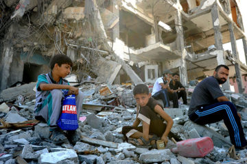palestinians sitting on the rubble of bombed building