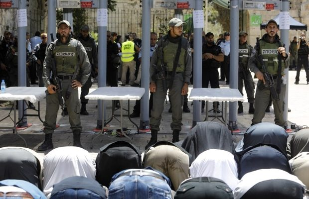 foreground muslim worshippers kneeling and in the background Israeli police officers next to metal detectors