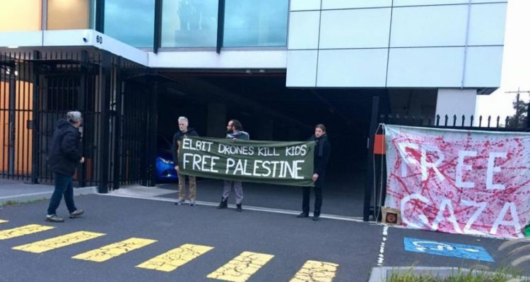 protesters holding free palestine sign outside the entrance to the Elbit office