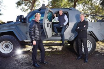 3 men standing with a heavily fortified vehicle