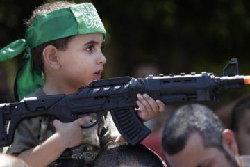 small palestinian boy holding fake gun