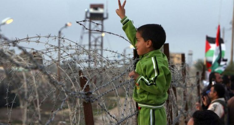 small palestinian boy standing next to a barbed wire fence with lookout tower in distance, holding his hand up in a peace sign
