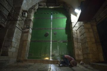 arab praying on floor in front of closed gate in old city