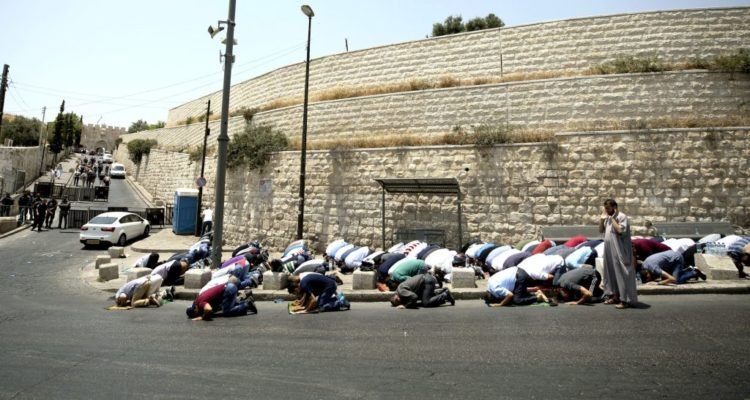 street corner with old city walls behind, and many moslems on floor praying