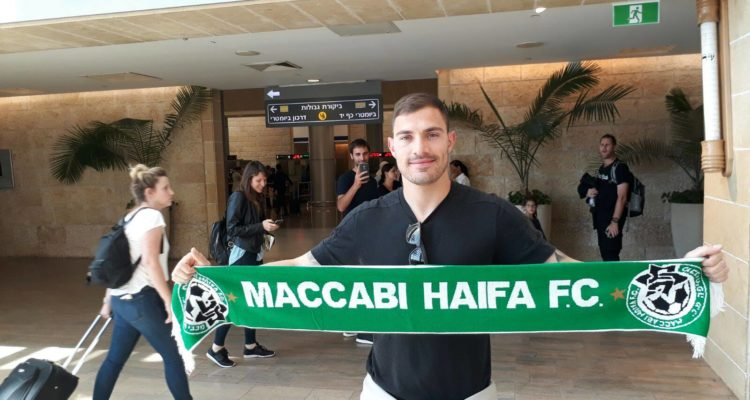 Troisi arriving at Ben Gurion airport holding up a Maccabi Haifa scarf