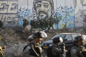 Israeli soldiers in front of separation wall with mural of arafat on it
