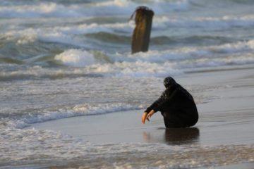 palestinian woman crouching on shore