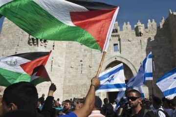 people waving israeli and palestinian flags outside the old city of jerusalem