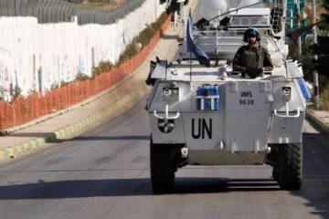 UN tank driving alongside a border fence