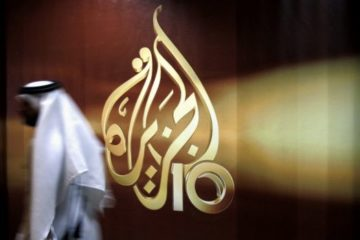 someone walking by al-jazeera logo on window