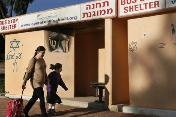 An Israeli mother passes by a bus stop which also serves as a bomb shelter as she accompanies her daughter to school in the Israeli southern city of Sderot