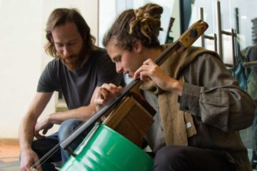 the two musicians playing the makeshift instrument