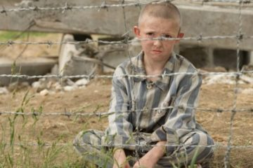 boy sitting in pyjamas behind barbed wire. still from movie