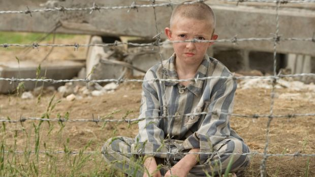 boy sitting in pyjamas behind barbed wire. still from movie