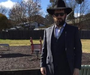Rabbi standing awkwardly in front of a playground