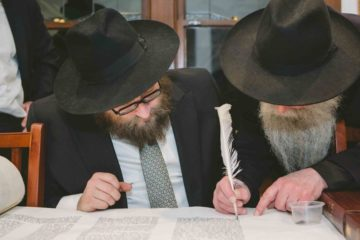 rabbis sitting finishing the torah scroll