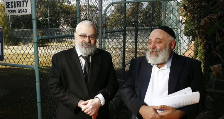 the two rabbis standing in front of the tennis courts