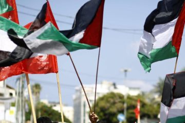 Palestinian flags being waved on a march