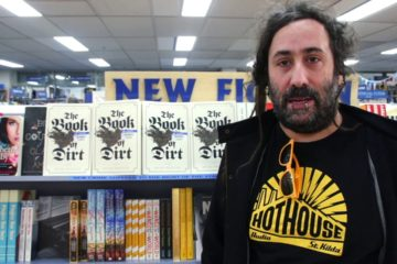 bram standing in front of his book on a shelf in a bookshop
